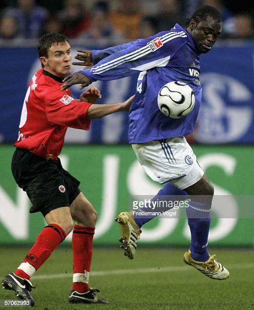 Aleksandar Vasoski of Frankfurt challenges for the ball with Gerald Asamoah of Schalke during the Bundesliga match between FC Schalke 04 and...