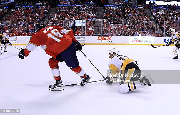Aleksander Barkov of the Florida Panthers and Nick Bonino of the Pittsburgh Penguins fight for the puck during a game at BBT Center on December 8...