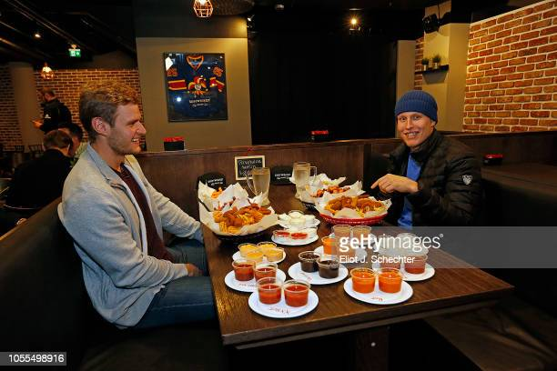 Aleksander Barkov of the Florida Panthers and Patrik Laine of the Winnipeg Jets have a friendly meal of chicken wings together at Siipiweikot their...