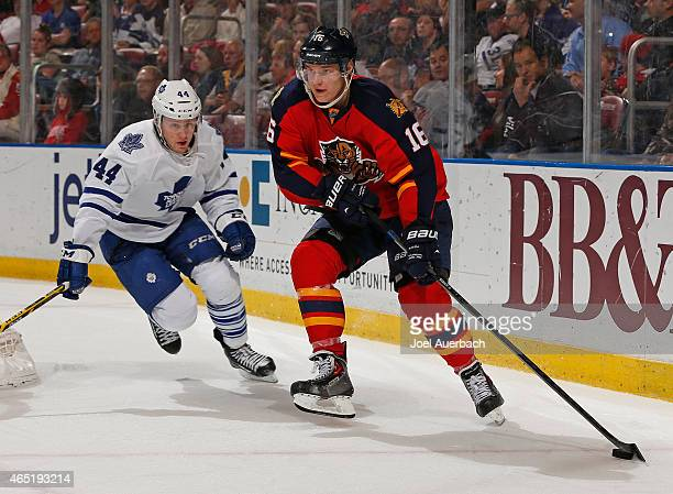 Aleksander Barkov of the Florida Panthers attempts to pass the puck as Morgan Rielly of the Toronto Maple Leafs circles the net to defend during...