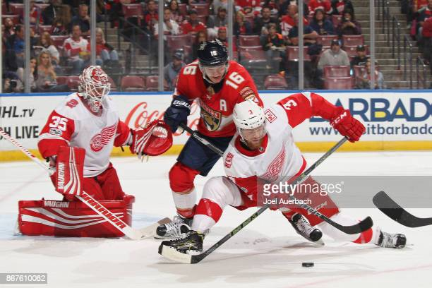 Aleksander Barkov of the Florida Panthers battles for control of the puck with Nick Jensen in front of goaltender Jimmy Howard of the Detroit Red...