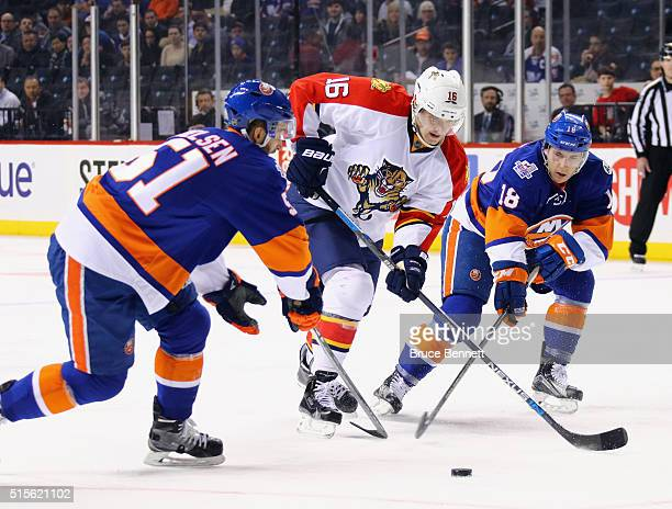 Aleksander Barkov of the Florida Panthers carries the puck past Frans Nielsen and Ryan Strome of the New York Islanders during the first period at...