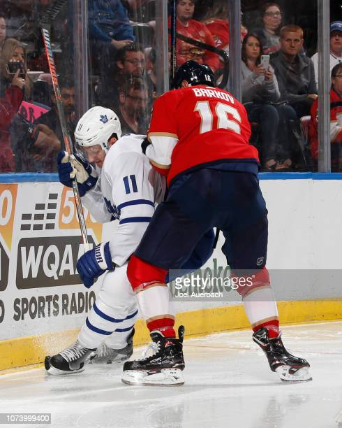 Aleksander Barkov of the Florida Panthers checks Zach Hyman of the Toronto Maple Leafs into the boards behind the net during second period action at...
