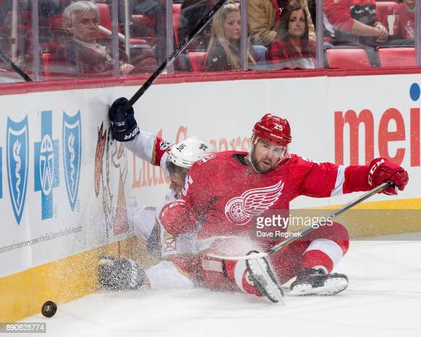 Aleksander Barkov of the Florida Panthers crashes into the boards with Mike Green of the Detroit Red Wings during an NHL game at Little Caesars Arena...