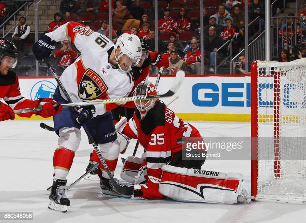 Aleksander Barkov of the Florida Panthers deflects the puck during the first period but it goes wide of Cory Schneider of the New Jersey Devils at...