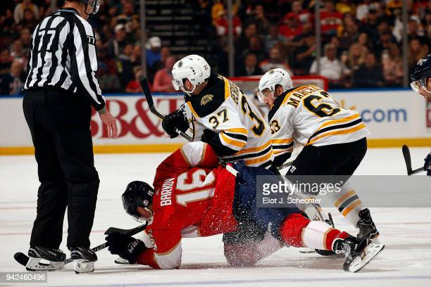 Aleksander Barkov of the Florida Panthers faces off against Patrice Bergeron of the Boston Bruins at the BBT Center on April 5 2018 in Sunrise Florida