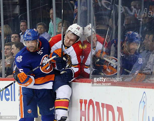 Aleksander Barkov of the Florida Panthers is checked into the boards by Johnny Boychuk of the New York Islanders during the first period in Game Six...