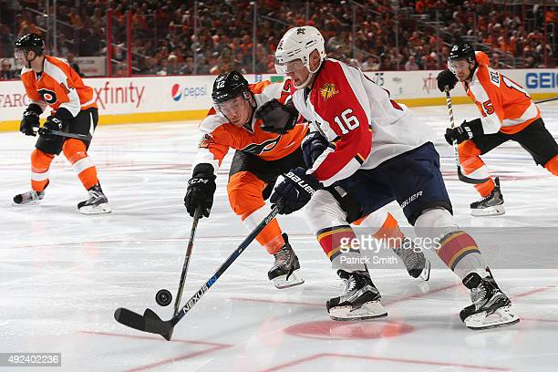 Aleksander Barkov of the Florida Panthers loses control of the puck as he is defended by Michael Raffl of the Philadelphia Flyers in the third period...