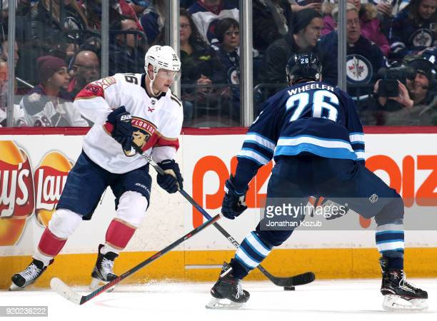 Aleksander Barkov of the Florida Panthers plays the puck along the boards as Blake Wheeler of the Winnipeg Jets defends during second period action...