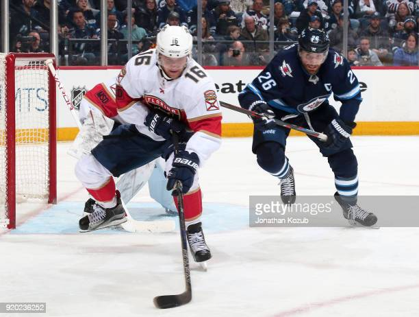 Aleksander Barkov of the Florida Panthers plays the puck as Blake Wheeler of the Winnipeg Jets gives chase during second period action at the Bell...