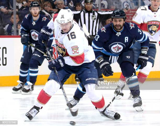 Aleksander Barkov of the Florida Panthers plays the puck away from Dustin Byfuglien of the Winnipeg Jets at the Bell MTS Place on February 18 2018 in...