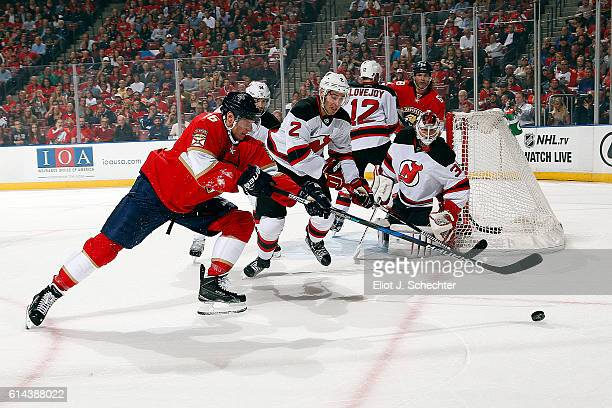 Aleksander Barkov of the Florida Panthers skates for possession against John Moore of the New Jersey Devils during first period action at the BBT...