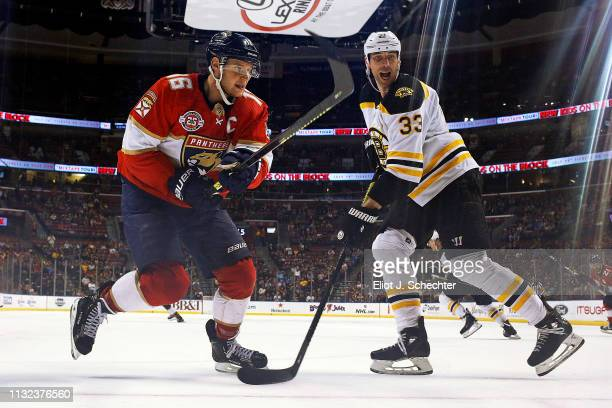 Aleksander Barkov of the Florida Panthers skates for possession against Zdeno Chara of the Boston Bruins at the BBT Center on March 23 2019 in...