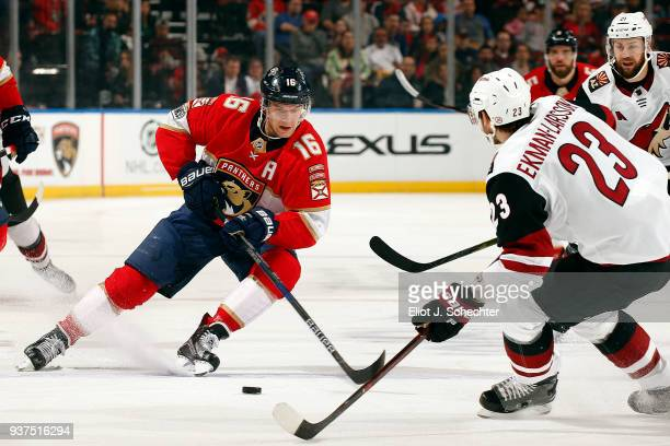 Aleksander Barkov of the Florida Panthers skates for possession against Oliver EkmanLarsson of the Arizona Coyotes at the BBT Center on March 24 2018...