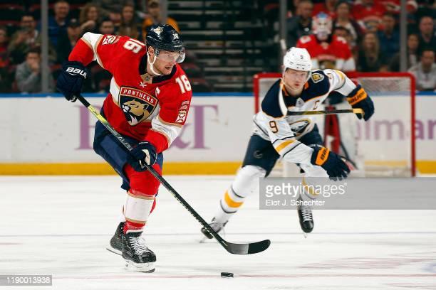 Aleksander Barkov of the Florida Panthers skates with the puck against Jack Eichel of the Buffalo Sabres at the BB&T Center on November 24, 2019 in...