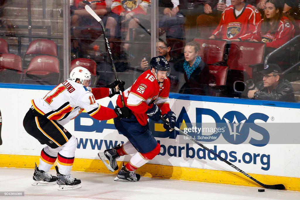 Aleksander Barkov #16 of the Florida Panthers skates with the puck against Mikael Backlund #11 of the Calgary Flames at the BB&T Center on January 12, 2018 in Sunrise, Florida.