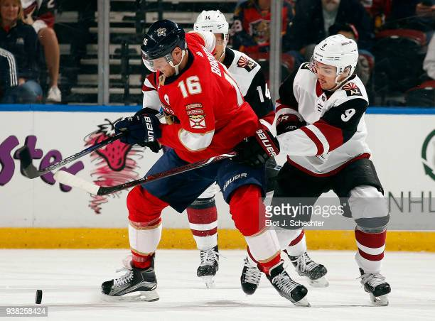 Aleksander Barkov of the Florida Panthers skates with the puck against Clayton Keller of the Arizona Coyotes at the BBT Center on March 24 2018 in...