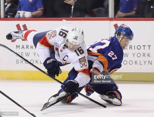 Aleksander Barkov of the Florida Panthers topples over Anders Lee of the New York Islanders during the third period at the Barclays Center on October...
