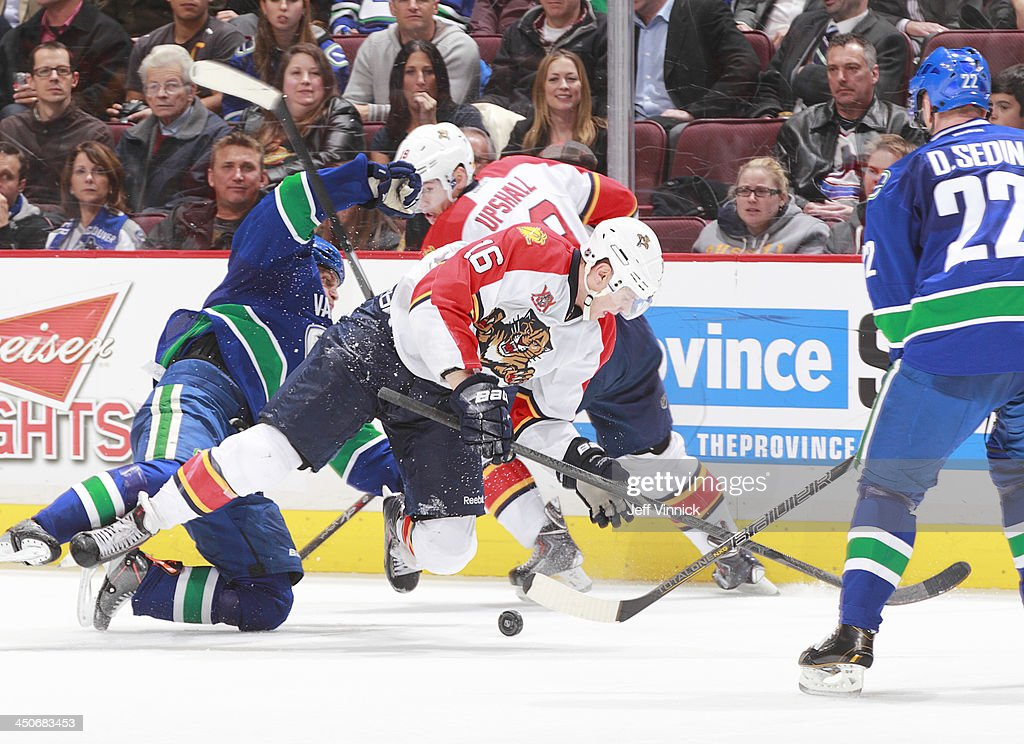Aleksander Barkov #16 of the Florida Panthers trips and Daniel Sedin #22 of the Vancouver Canucks waits for the puck during their NHL game at Rogers Arena on November 19, 2013 in Vancouver, British Columbia, Canada. Florida won 3-2 in a shootout.
