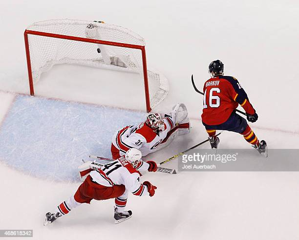 Aleksander Barkov of the Florida Panthers watches as his shot goes over the outstretched leg of Goaltender Anton Khudobin of the Carolina Hurricanes...
