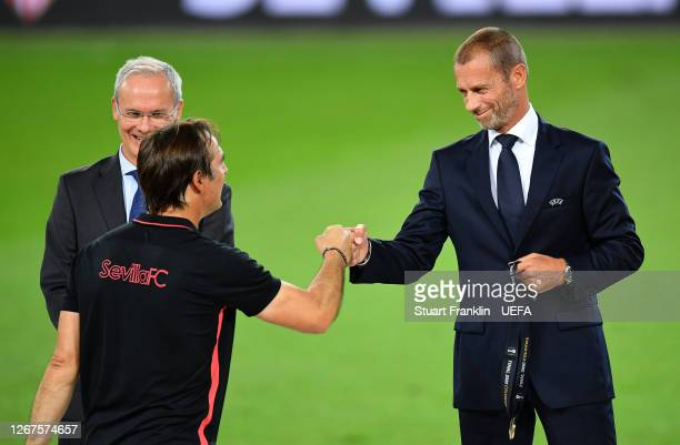 Aleksander Ceferin President of UEFA bumps fists with Julen Lopetegui Head Coach of Sevilla as he presents him with his winners medal following the...