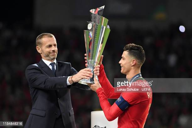 Aleksander Ceferin UEFA President hands Cristiano Ronaldo of Portugal the UEFA Nations League Trophy following his team's victory in the UEFA Nations...