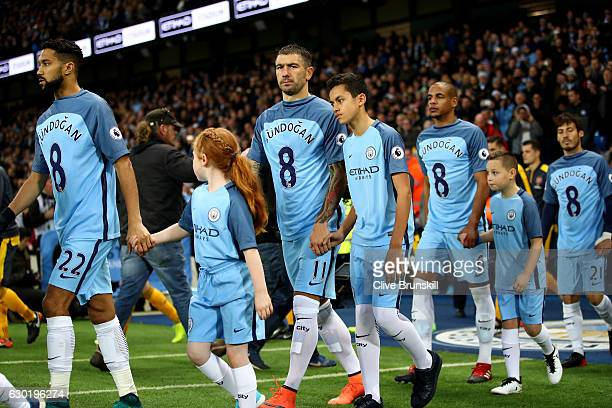 Aleksander Kolorov of Manchester City and his Manchester City team mates wear Ilkay Gundogan of Manchester City shirt in surport for him after he was...