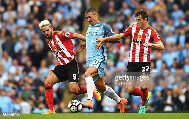 Aleksander Kolorov of Manchester City battle for possession with Fabio Borini of Sunderland and Donald Love of Sunderland during the Premier League...