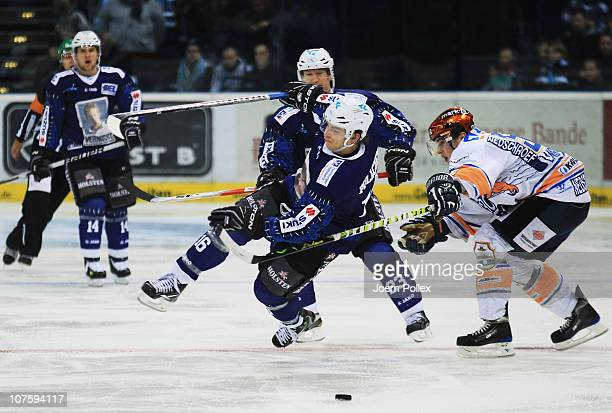 Aleksander Polaczek of Hamburg vies for the puck with Stefan Langwieder of Iserlohn during the DEL match between Hamburg Freezers and Iserlohn...