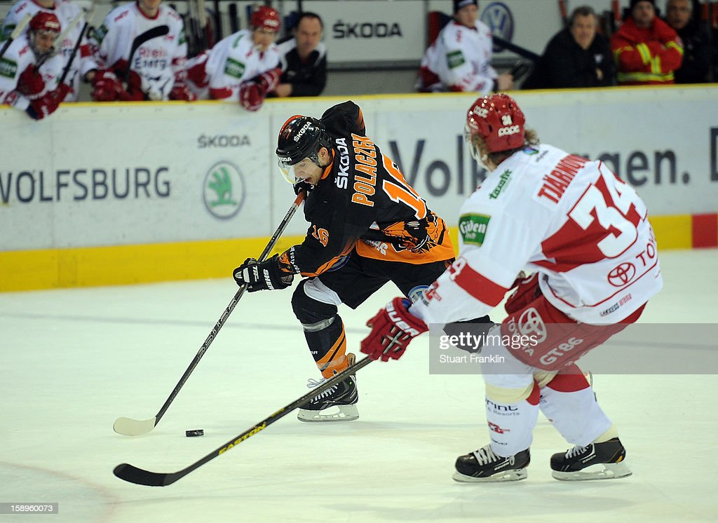 Aleksander Polaczek of Wolfsburg challenges for the puck with Daniel Tjemqvist of Cologne during the DEL match between Grizzly Adams Wolfsburg and Kolner Haie at the Volksbank BraWo Eisarena on January 4, 2013 in Wolfsburg, Germany
