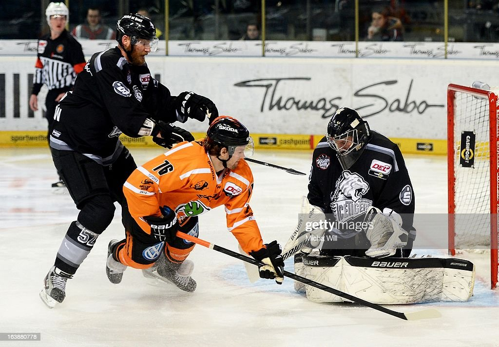 Aleksander Polaczek (C) of Wolfsburg challenges goalie Andreas Jenike (R) and Sven Butenschoen of Nuremberg during game three of the DEL pre-play-offs between Thomas Sabo Ice Tigers and Grizzly Adams Wolfsburg on March 17, 2013 in Nuremberg, Germany.