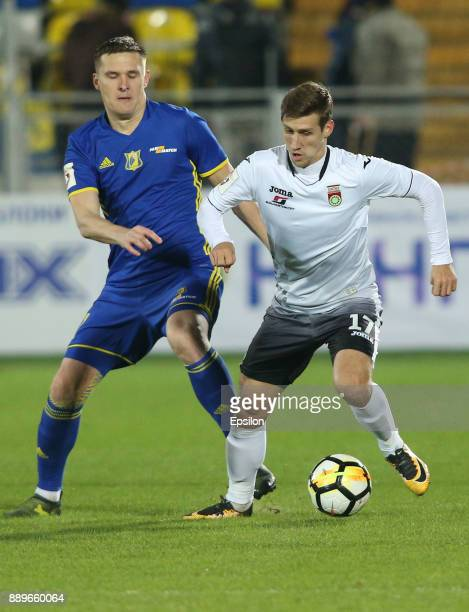 Aleksandr Bukharov of FC Rostov RostovonDon vies for the ball with Dmitri Zhivoglyadov of FC Ufa during the Russian Premier League match between FC...