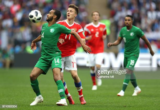 Aleksandr Golovin of Russia and Abdullah Otayf of Saudi Arabia challenge for the ball during the 2018 FIFA World Cup Russia Group A match between...