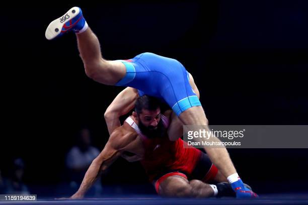 Aleksandr Golovin of Russia and Revazi Nadareishvili of Georgia compete in the Men's Greco-Roman -97kg Bronze Medal match or bout during Day Ten of...