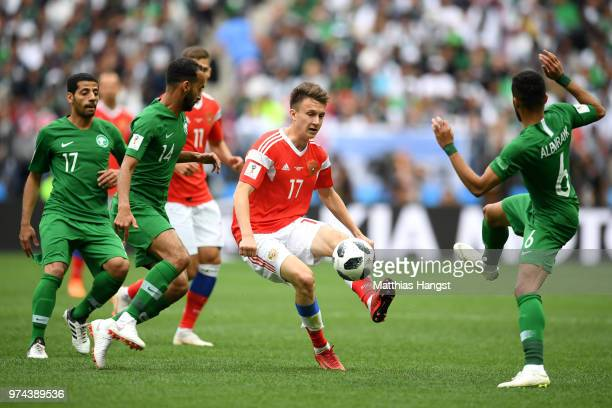 Aleksandr Golovin of Russia controls the ball under pressure of Mohammed Alburayk Abdullah Otayf and Taiseer Aljassam of Saudi Arabia during the 2018...