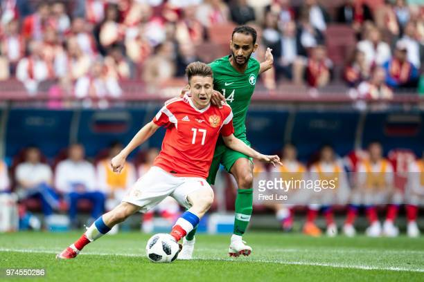 Aleksandr Golovin of Russia is challenged by Abdullah Otayf of Saudi Arabia during the 2018 FIFA World Cup Russia Group A match between Russia and...