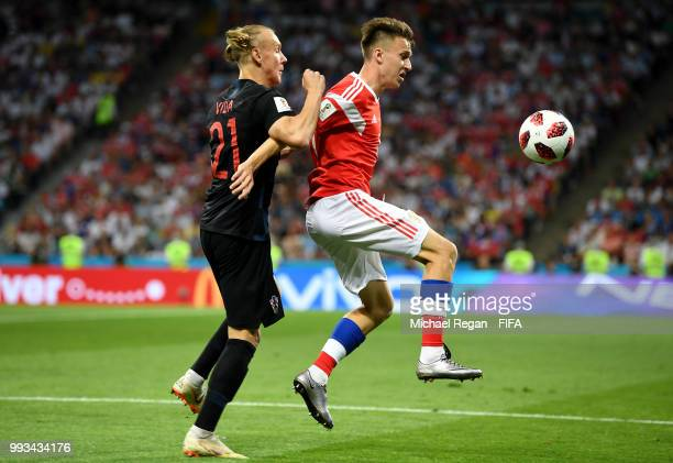 Aleksandr Golovin of Russia is challenged by Domagoj Vida of Croatia during the 2018 FIFA World Cup Russia Quarter Final match between Russia and...