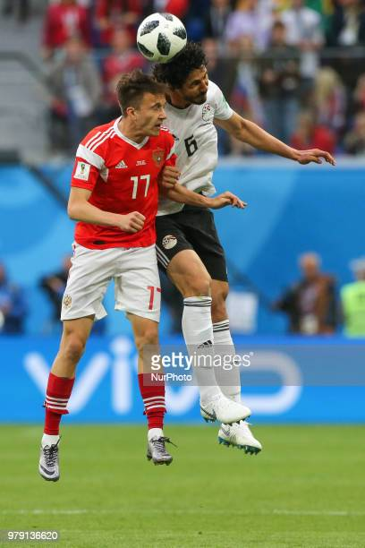 Aleksandr Golovin of the Russia national football team and Ahmed Hegazy of the Egypt national football team vie for the ball during the 2018 FIFA...