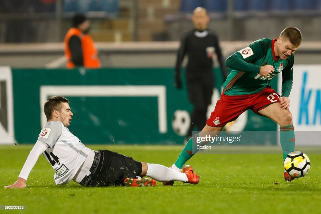 Aleksandr Karnitsky (L) of FC Tosno and Igor Denisov of FC Lokomotiv Moscow vie for the ball during the Russian Football League match between FC Tosno and FC Lokomotiv Moscow on December 11, 2017 at Petrovsky Stadium in Saint Petersburg, Russia.