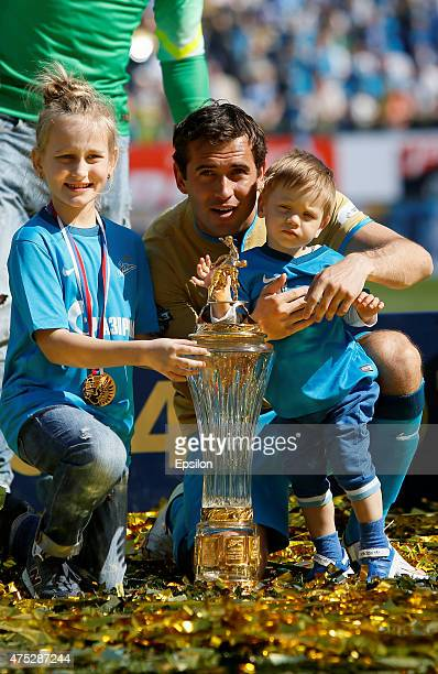 Aleksandr Kerzhakov of FC Zenit St Petersburg and his children with the trophy as Zenit players celebrate the Russian Championship title after the...