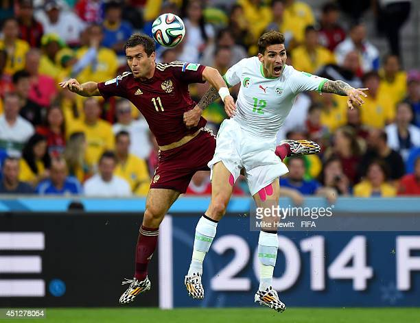 Aleksandr Kerzhakov of Russia and Carl Medjani of Algeria compete for the ball during the 2014 FIFA World Cup Brazil Group H match between Algeria...