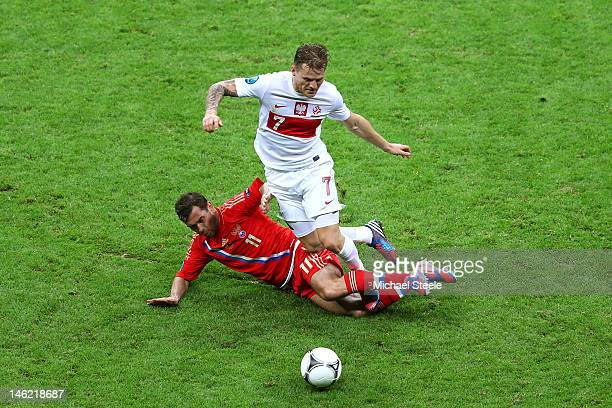 Aleksandr Kerzhakov of Russia tackles Eugen Polanski of Poland during the UEFA EURO 2012 group A match between Poland and Russia at The National...
