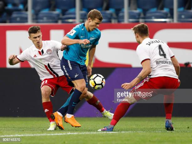 Aleksandr Kokorin of FC Zenit Saint Petersburg vies for the ball with Aleksandr Ryazantsev and Nikolai Zaytsev of FC Amkar Perm during the Russian...