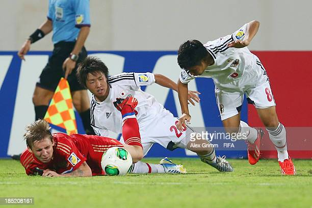 Aleksandr Makarov of Russia is challenged by Daisuke Sakai and Taro Sugimoto of Japan during the FIFA U17 World Cup UAE 2013 Group D match between...