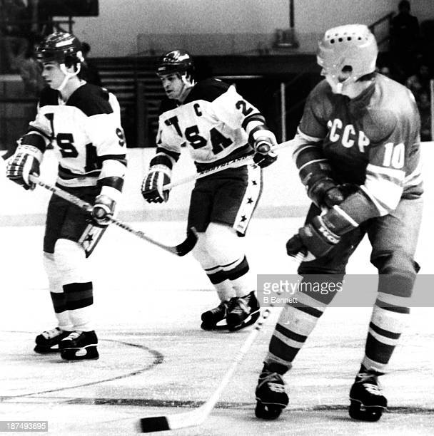 Aleksandr Maltsev of the USSR shoots as Neal Broten and Mike Eruzione of Team USA look for the rebound during an 1980 exhibition game on February 9...