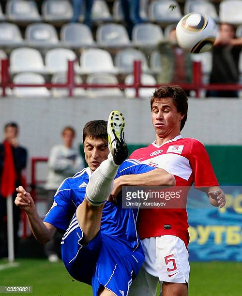 Aleksandr Sheshukov of FC Spartak Moscow battles for the ball with Goran Maznov of FC Tom Tomsk during the Russian Football League Championship match...
