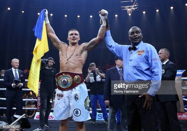 Aleksandr Usyk of Ukraine celebrates after winning the WBO Cruiserweight World Boxing Super Series fight against Marco Huck of Germany next to...