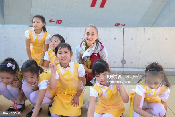 Aleksandra Krunic of Serbia poses for a picture with kids during the Little Painter event on day three of 2018 China Open at the China National...