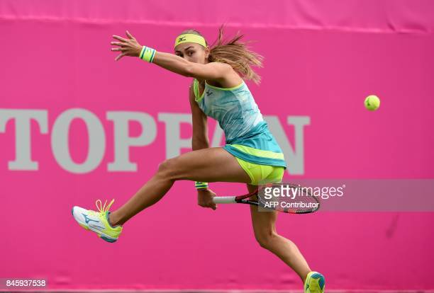 Aleksandra Krunic of Serbia returns a shot between her legs to Kimiko Date of Japan during their first round match of the Japan Women's Open tennis...