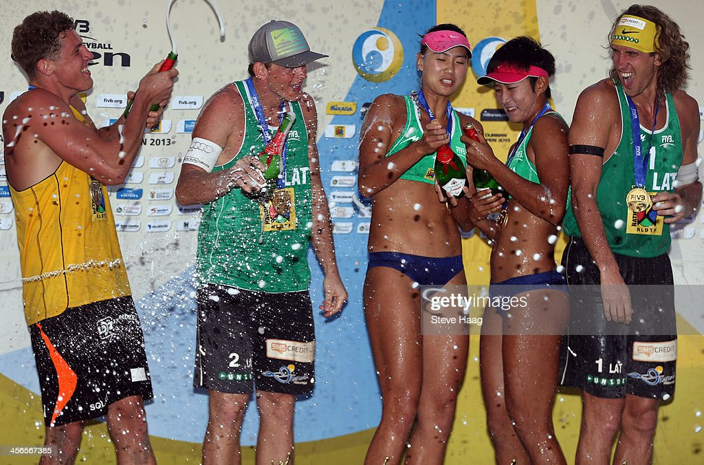 Aleksandrs Solovejs of Latvia, Janis Smedins of Latvia, Chen Xue and Xinyi Xia of China, and Aleksandrs Samoilovs of Latvia spray champagne during the medals ceremony at the FIVB Durban Open at New Beach on December 14, 2013 in Durban, South Africa.